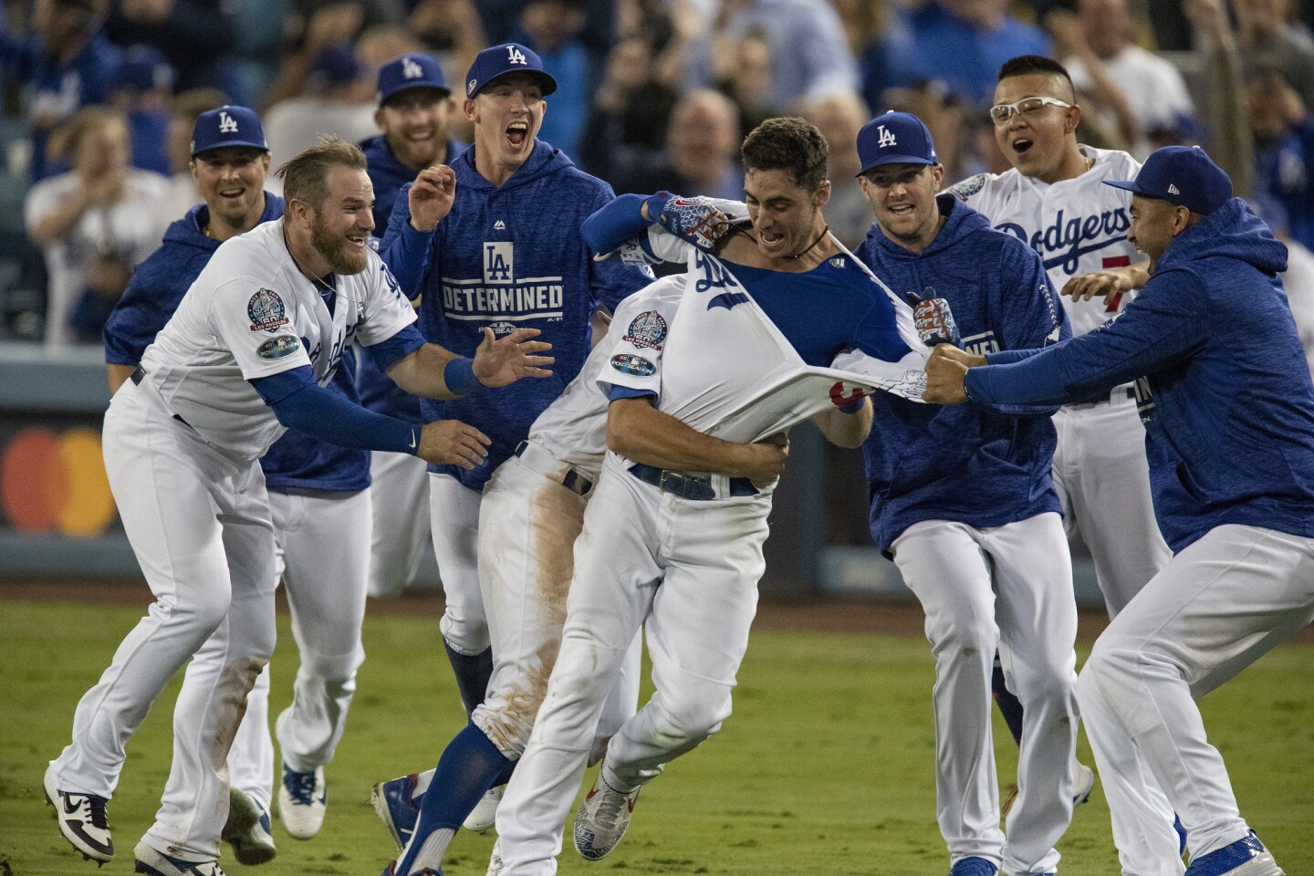 Teammates mob Dodgers center fielder Cody Bellinger after he hit the game winning RBI in the 13th inning during Game 4 of the NLCS at Dodger Stadium on October 16, 2018.