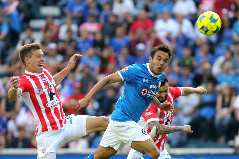El jugador de Cruz Azul, Omar Mendoza, disputa el balón con Claudio Riaño y con Luis Gallegos, del Necaxa, durante el partido de la jornada inicial del Torneo Clausura del fútbol mexicano realizado en el Estadio Azul, en Ciudad de México.