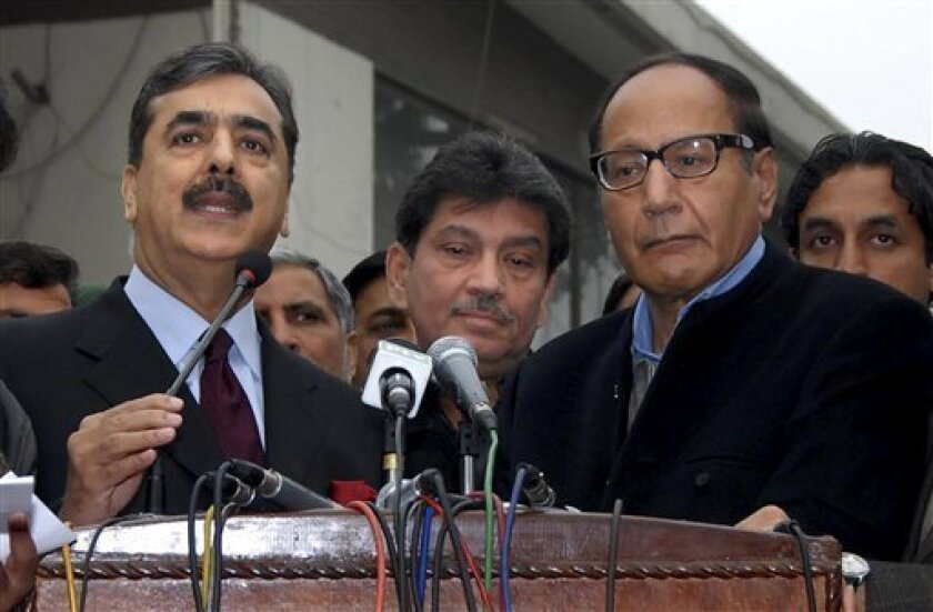 Prime Minister of Pakistan Yousuf Raza Gilani, left, talks to media after his meeting with political leader and former Prime Minister Chaudary Shujjat Hussain, front right, in Lahore, Pakistan on Monday, Jan. 3, 2011. Gilani tried to keep his government from collapsing after a key party said it was quitting the ruling coalition, leaving the government short of majority support in parliament. (AP Photo)