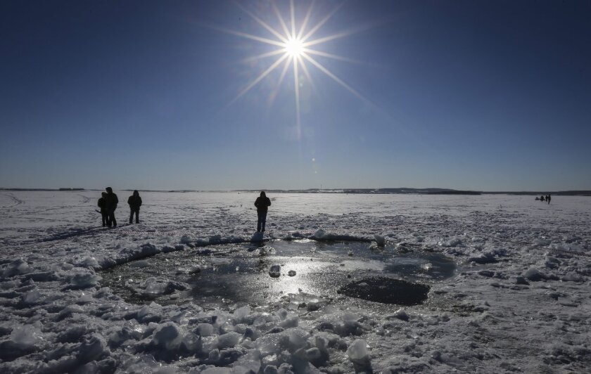 Russian people stand near a giant hole in frozen Lake Chebarkul that was reportedly made by a meteorite from the Chelyabinsk fireball in February.