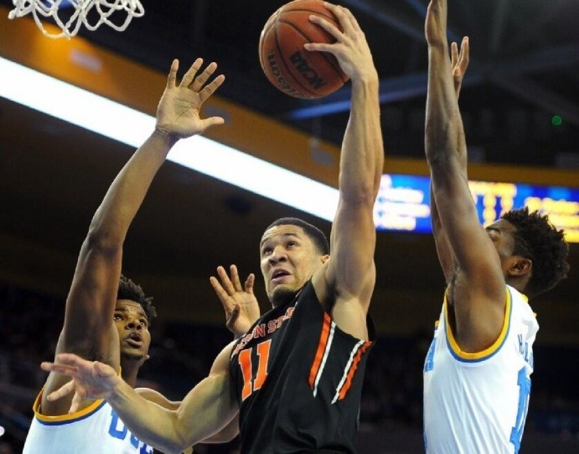 Oregon State guard Malcolm Duvivier goes to the hoop against UCLA forward Tony Parker, left, and guard Isaac Hamilton during a game on March 5 at Pauley Pavilion.