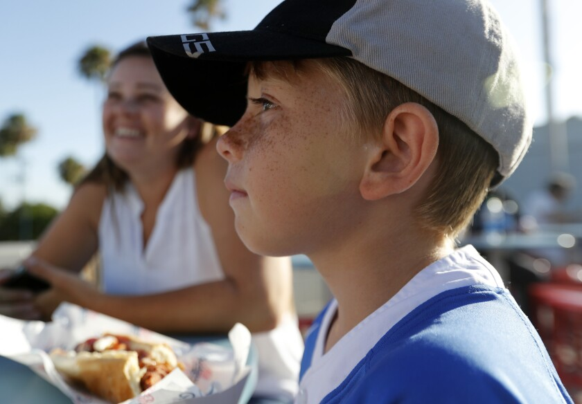 Mychal and Liam Schottler, of Long Beach, munch on Dodger Dogs