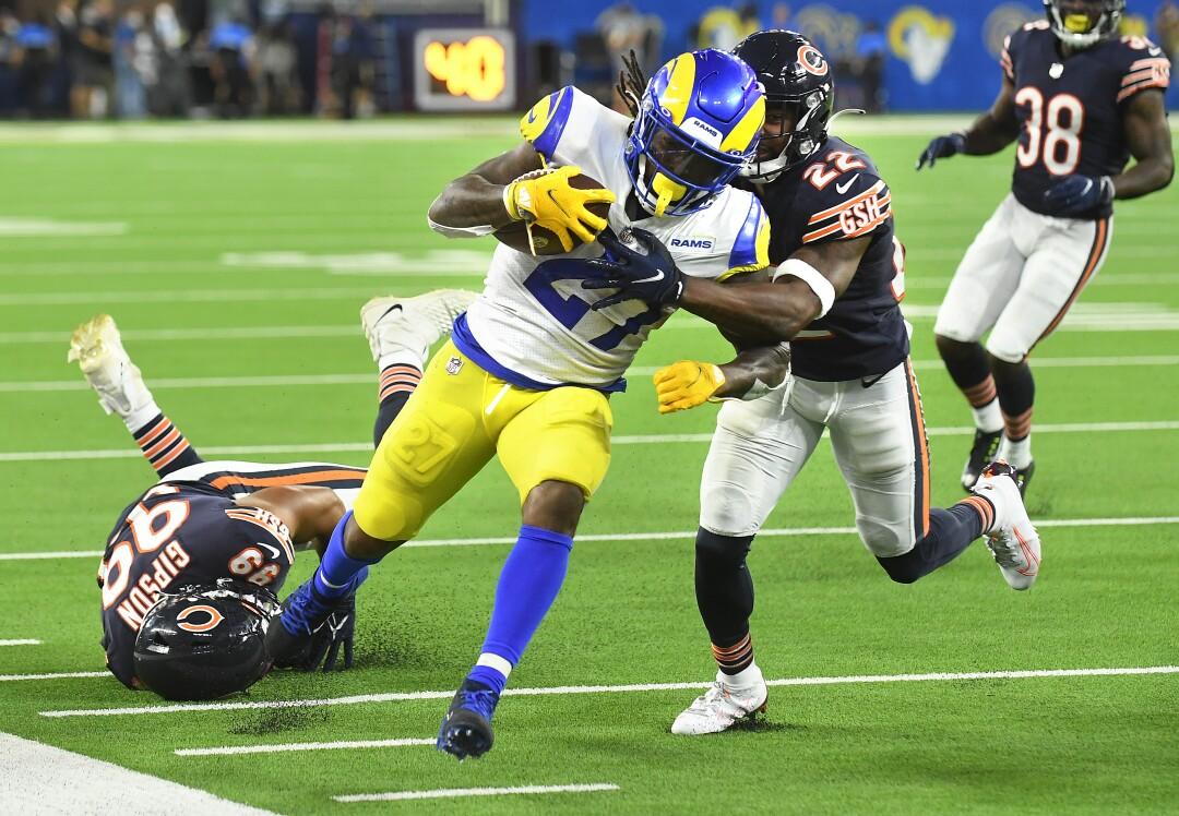 Le porteur de ballon des Rams de Los Angeles Darrell Henderson est poussé hors des limites par les arrières défensifs des Bears de Chicago Kindle Vildor