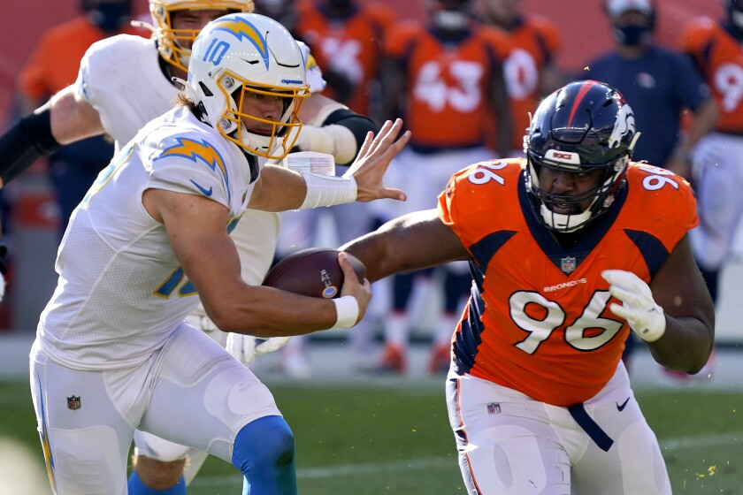 Los Angeles Chargers quarterback Justin Herbert (10) runs as Denver Broncos defensive end Shelby Harris (96) pursues during the first half of an NFL football game, Sunday, Nov. 1, 2020, in Denver. (AP Photo/David Zalubowski)