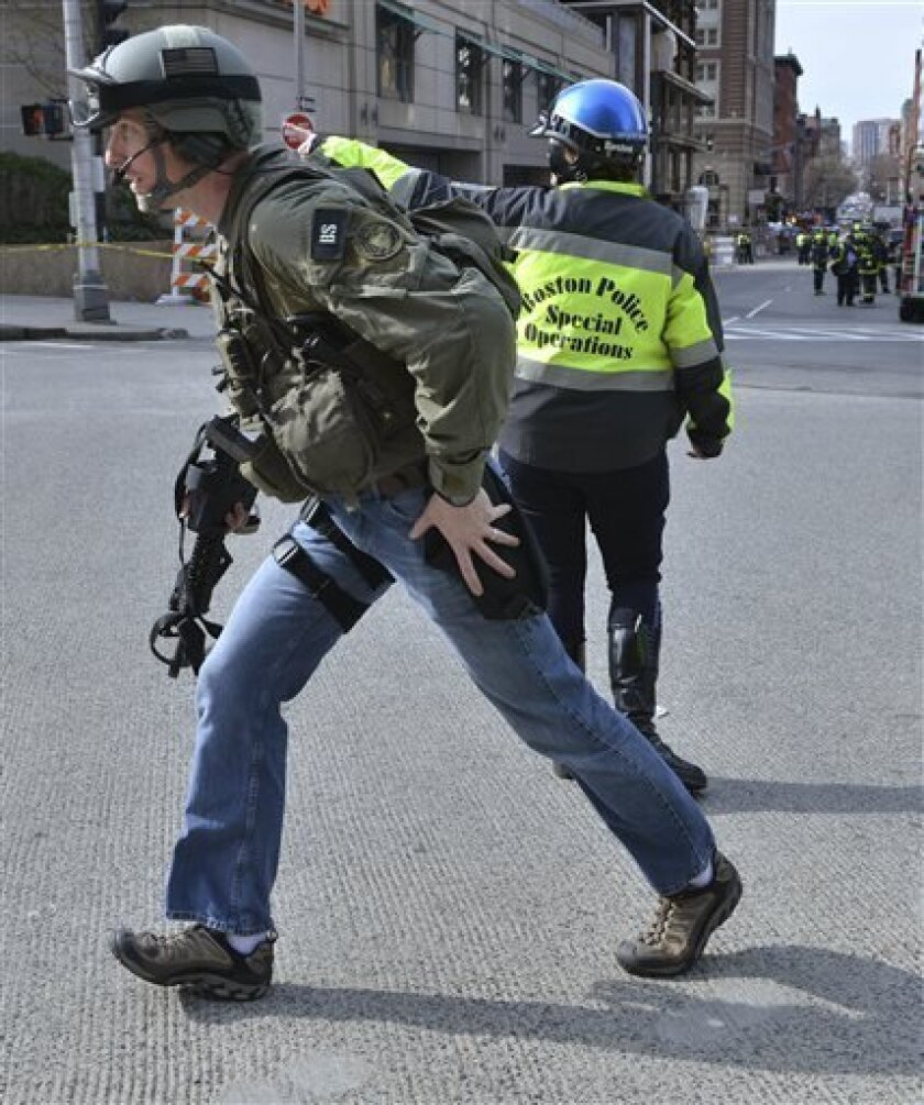An armed FBI agent passes a Boston police officer following an explosion at the finish line of the 2013 Boston Marathon in Boston, Monday, April 15, 2013. Two explosions shattered the euphoria of the Boston Marathon finish line on Monday, sending authorities out on the course to carry off the injured while the stragglers were rerouted away from the smoking site of the blasts. (AP Photo/Josh Reynolds)