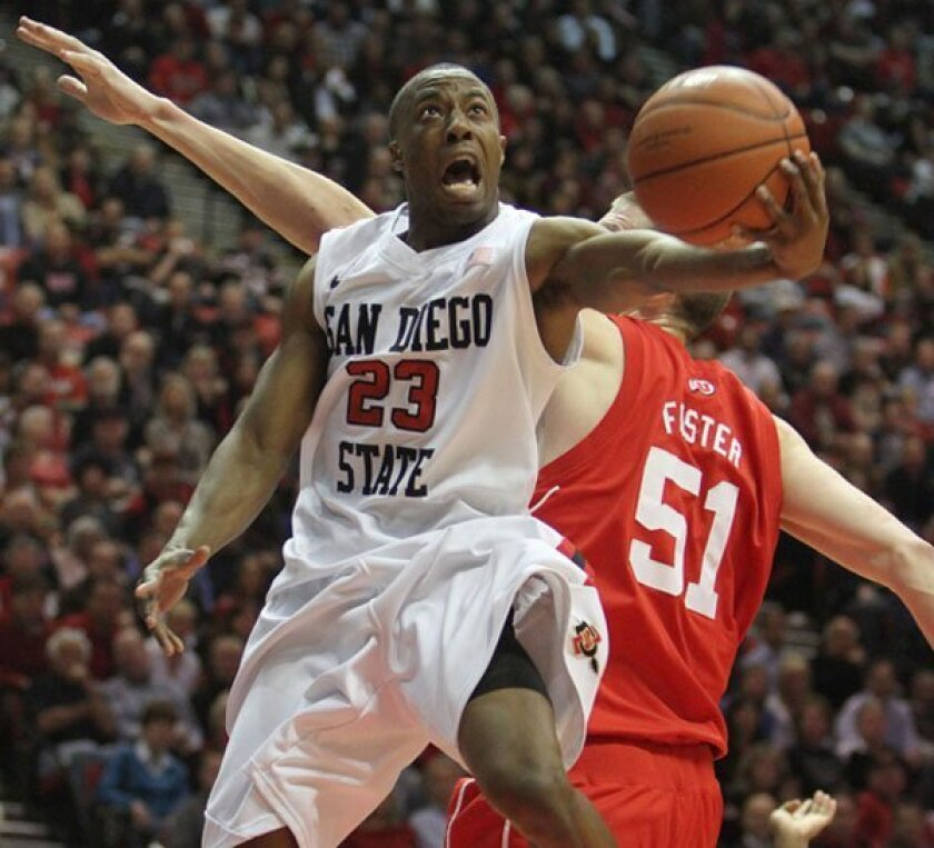Aztecs DJ Gay goes airborne to elude David Foster of University of Utah for two points in San Diego's win last month at Viejas Arena.
