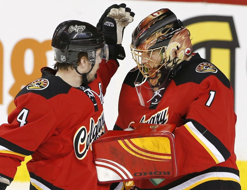 Calgary Flames goalie Jonas Hiller, right, from Switzerland, celebrates with teammate Kris Russell a 4-3 victory over the Toronto Maple Leafs in Calgary, Alberta, Tuesday, Feb. 9, 2016. (Larry MacDougal/The Canadian Press via AP) MANDATORY CREDIT