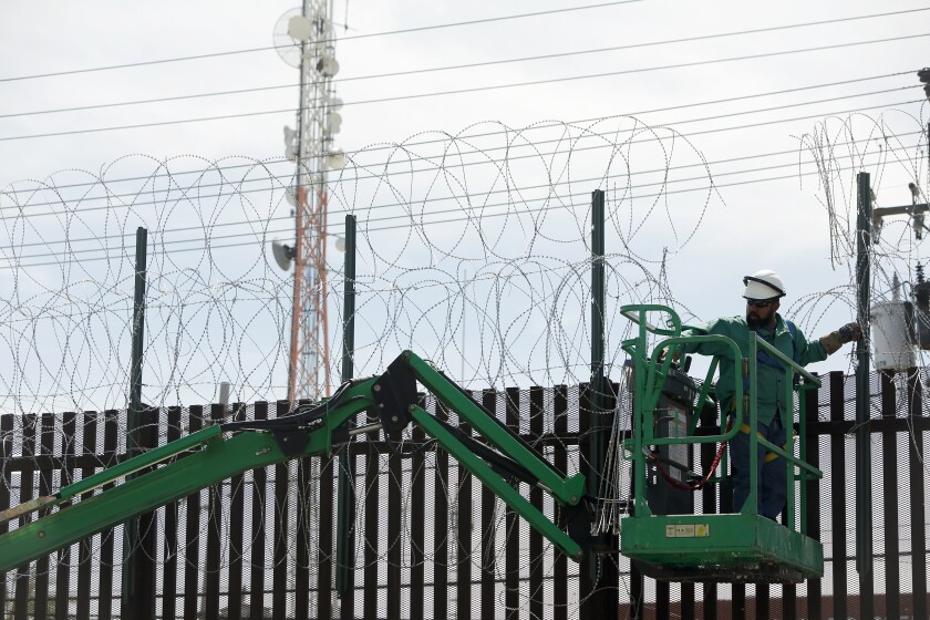 A man with Cerrudo Services replaces a cut section of the border fence from people crossing over in Calexico, California. President Donald Trump will be in Calexico on Friday to visit a newly completed section of the border barrier that replaced the previous one.