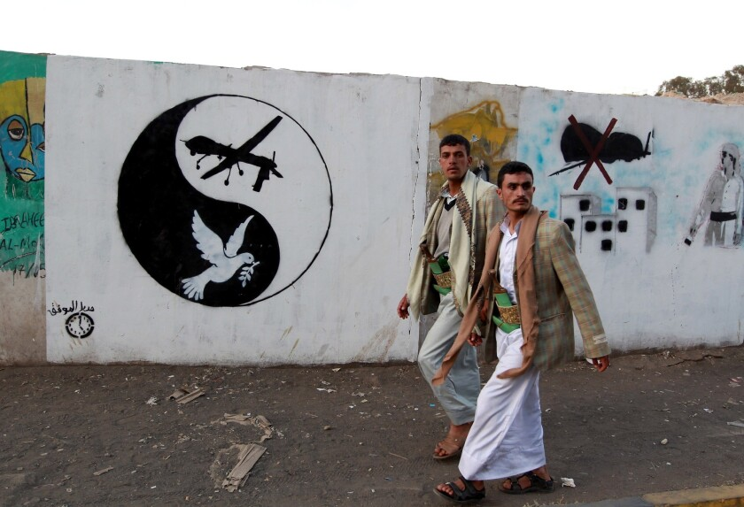 Yemeni men walk past a mural depicting a U.S. drone and a dove in a yin-yang symbol on Friday in the capital city of Sana.