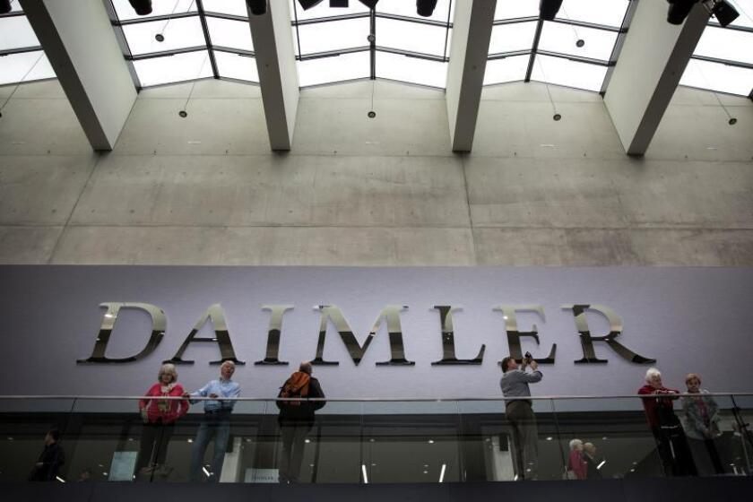 Varias personas permanecen junto al logotipo del fabricante automovilístico alemán Daimler. EFE/ Omer Messinger/Archivo