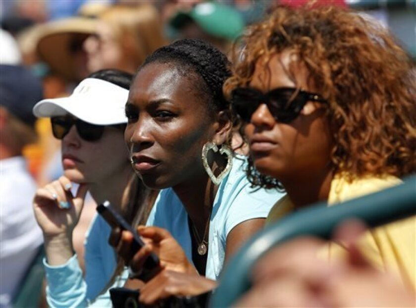 Venus Williams, center, watches her sister, Serena Williams, play Jelena Jankovic, of Serbia, during the singles final at the Family Circle Cup tennis tournament in Charleston, S.C., Sunday, April 7, 2013.  Williams defeated Jankovic, 3-6, 6-0, 6-2, to win the Family Circle Cup. (AP Photo/Mic Smith