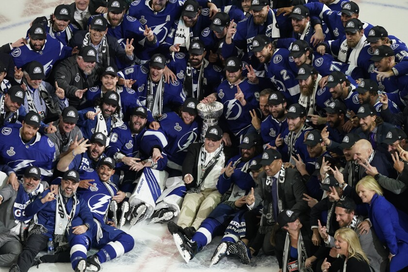 The Tampa Bay Lightning team poses with the Stanley Cup after Game 5 of the NHL hockey Stanley Cup finals against the Montreal Canadiens, Wednesday, July 7, 2021, in Tampa, Fla. (AP Photo/Gerry Broome)