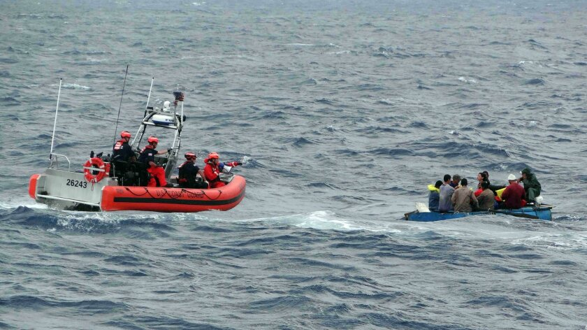 In this image taken on Jan. 4, 2016, released by the U.S. Coast Guard, Coast Guard personnel left, try to assist a group of Cuban migrants on a makeshift vessel in the Florida Straits. The U.S. Coast Guard says it's documenting increasing instances of violence and non-compliance at sea among Cuban migrants. (U.S. Coast Guard via AP)