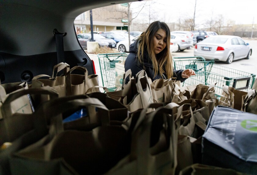 Alid Alvarado loads her car with orders for three different Instacart customers Tuesday, Dec. 4, 2018 at Whole Foods.