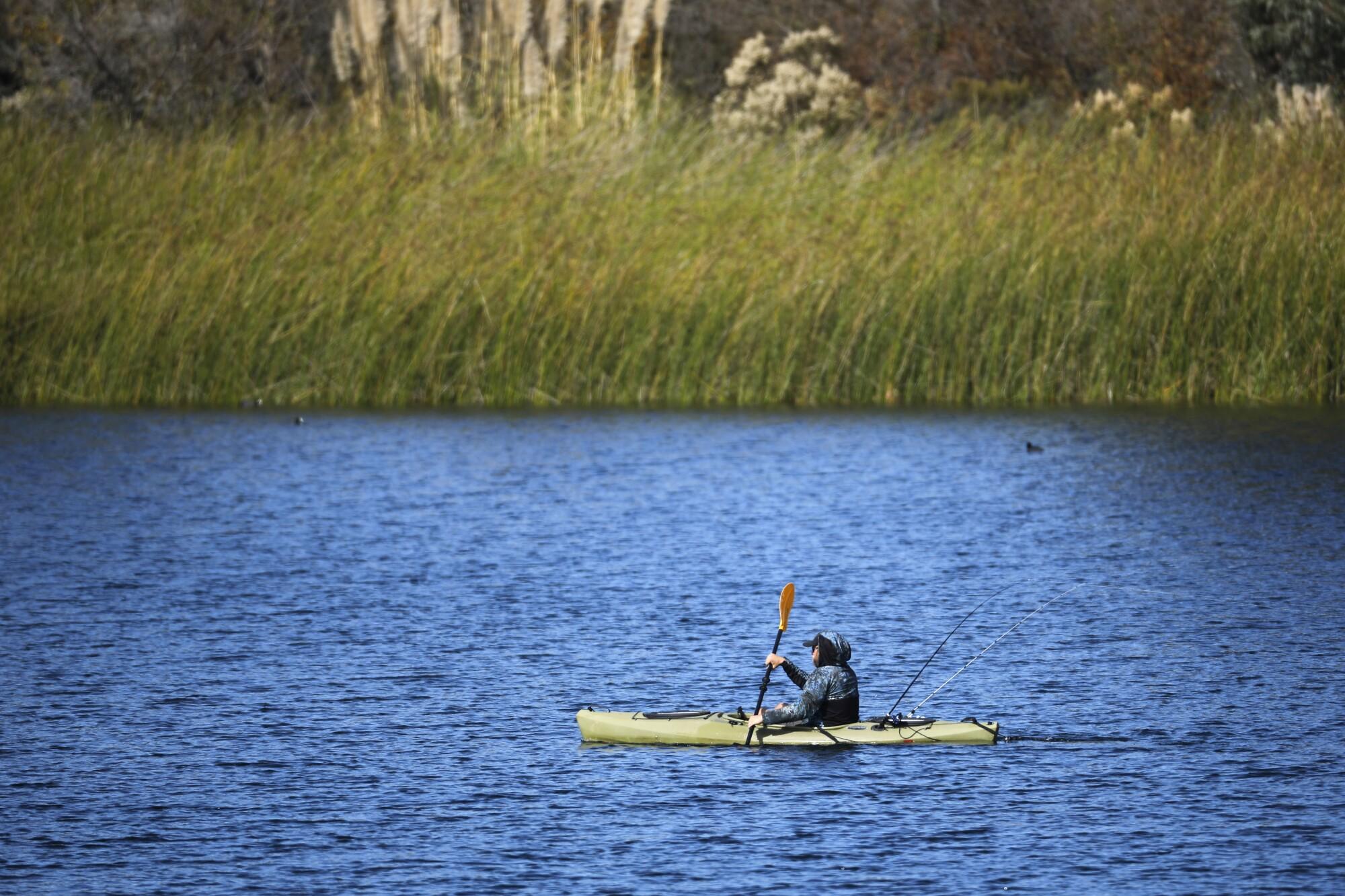 Justin Brackett kayaks along as he fishes on a hot morning in Miramar Reservoir.