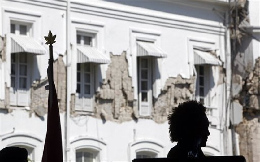 Canada's Governor General Michaelle Jean is silhouetted against the damaged National Palace during a joint news conference with Haiti's President Rene Preval, unseen, in Port-au-Prince, Monday, March 8, 2010. Jean is on her second visit to her homeland after the Jan. 12 devastating earthquake. (AP