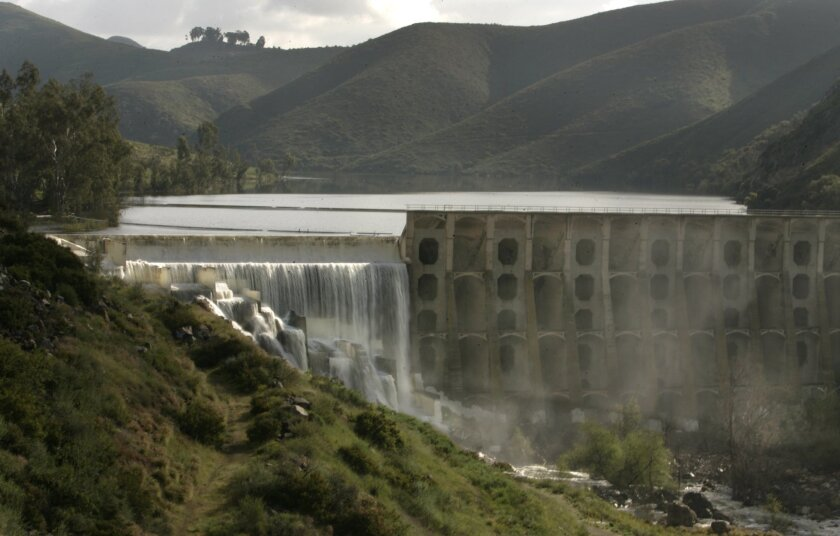 Lake Hodges is so full that water is topping the spillway -- a rare sight in the past five years. Water agencies are unsure how customers will respond to the combination of healthy water supplies, an improving economy and warm weather this summer.