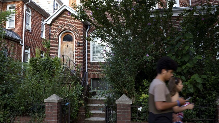 People pass by the residence of Nazi war crimes suspect Jakiw Palij in the Queens borough of New York on Tuesday.