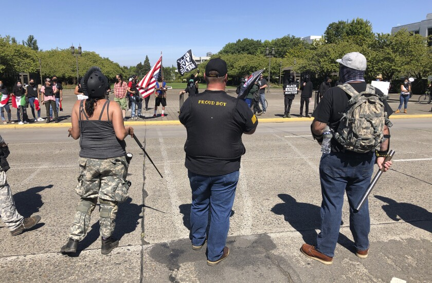 Supporters of President Donald Trump and Black Lives Matter protesters confront each other at the Oregon state Capitol in Salem, Ore. on Monday, Sept. 7, 2020. (AP Photo/Andrew Selsky)