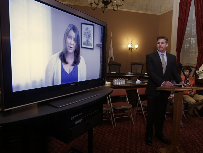 During a March 25 appearance at the California Capitol, Dan Diaz, the husband of Brittany Maynard, watches a video of his wife recorded 19 days before her assisted-suicide death. Diaz was at the Capitol again on Aug. 18, urging support for an aid-in-dying bill.