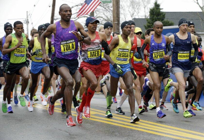 From left, Yemane Adhane Tsegay of Ethiopia, Wesley Korir of Kenya, Tadese Tola of Ethiopia, Meb Keflezighi of San Diego, Lelisa Desisa of Ethiopia, Lusapho April of South Africa, and Nicholas Arciniaga of Flagstaff, Ariz., leave the start line of the Boston Marathon, Monday, April 20, 2015, in Hopkinton, Mass. (AP Photo/Stephan Savoia)