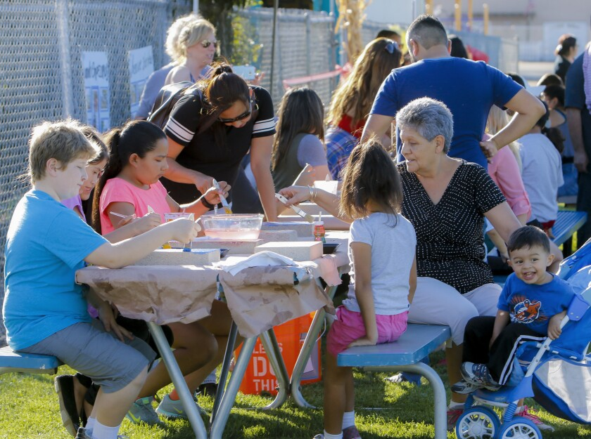 Students and their families decorate concrete pavers that will be in Central Elementary's new community garden, which was opened last week with a celebration that included a family picnic, music and games for students.