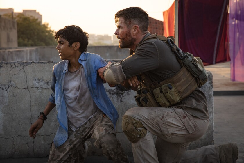 "Rudhraksh Jaiswal, left, and Chris Hemsworth in the Netflix action film ""Extraction"""