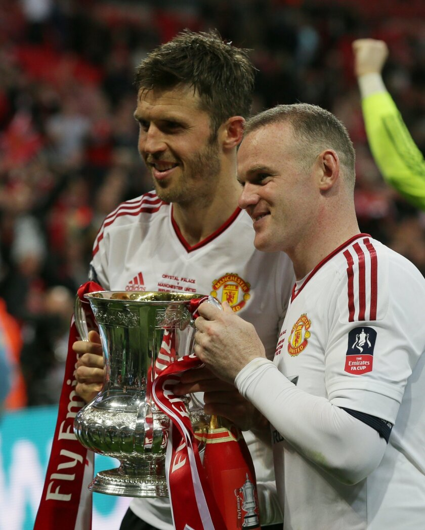 Manchester United's Wayne Rooney, right, and Michael Carrick pose with the trophy after winning the English FA Cup final soccer match against Crystal Palace at Wembley Stadium, London on Saturday May 21, 2016. Manchester United won the match 1-2. (AP Photo/Tim Ireland)