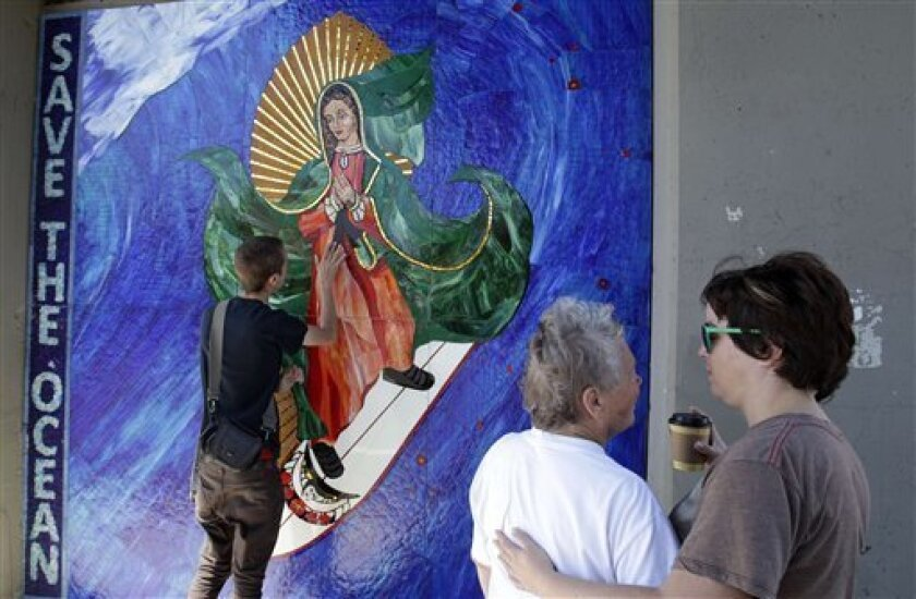 In this May 27, 2011 photo, Jules Itzkoff, of Cincinnati, Ohio, left, looks at an image of the Virgin of Guadalupe riding a surfbaord that hangs under a train bridge as Starr Culver, right, and Mary Martin, center, both of Leucadia, Calif., embrace in Encinitas, Calif. The unauthorized artwork is drawing a mass following, and even city officials who say she must go say they too have been taken by her. (AP Photo/Gregory Bull)
