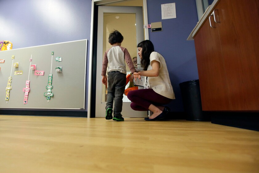 Megan Krail helps a 4-year-old boy with Autism Spectrum Disorder.