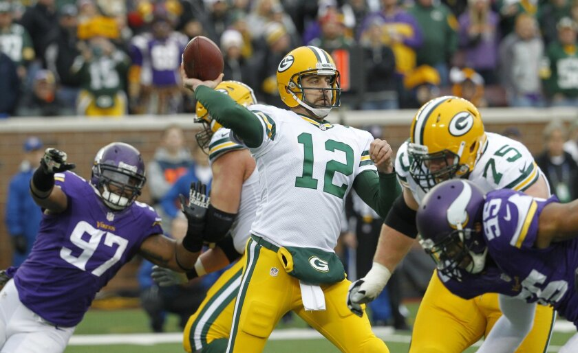 FILE - In this Sunday, Nov. 23, 2014 file photo, Green Bay Packers quarterback Aaron Rodgers (12) throws a pass during the second half of an NFL football game against the Minnesota Vikings in Minneapolis. For the last five years, Aaron Rodgers and the Green Bay Packers have had a firm grip on this border-state rivalry with the Minnesota Vikings that has otherwise been remarkably close. The Packers (6-3) will bring a sputtering offense, injured important players and a three-game losing streak to Minnesota (7-2), Sunday, Nov. 22, 2015 to face a well-rounded team that has won five games in a row to take over the NFC North lead. (AP Photo/Ann Heisenfelt, File)