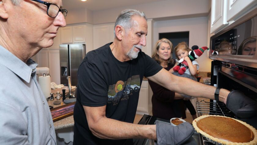Craig Coley removes pumpkin pies from the oven for Thanksgiving at his Carlsbad home. At left is investigator and former police officer Mike Bender. At right is Mike's wife Cyndi holding their granddaughter Keira Andrew, 3. Mike's efforts led to Craig's r