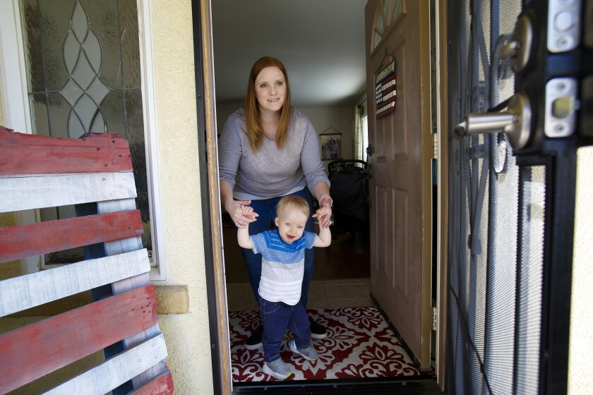 Charlie Luckesen, with help from his mother Katie Luckesen, walking to the front door of the family's home in South San Diego.