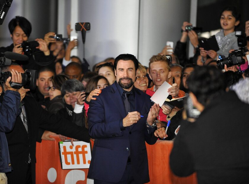 """Actor and cast member John Travolta interacts with the fans before the screening of """"The Forger"""" at the 39th annual Toronto International Film Festival."""