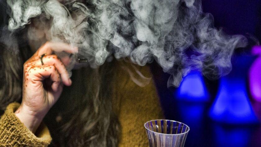 In this Saturday, Dec. 22, 2018 photo Crystal Feldman an event organizer takes a puff off a cannabis