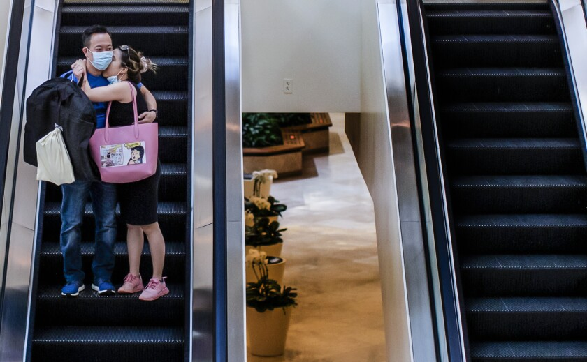 Couple embrace on escalator