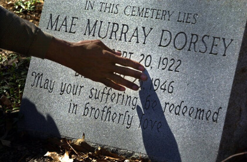 010226 - MONROE, GA -- A TOUCH OF REDEMPTION -- Bobby Howard, 60, touches a memorial tombstone for Moore's Ford lynching victim Mae Murray Dorsey during a visit to the Zion Hill Cemetery in Monroe, Ga., on Monday, Feb. 26, 2001. Dorsey was one of four blacks lynched nearby on July 25, 1946. (Curtis Compton/Atlanta Journal-Constitution via AP)