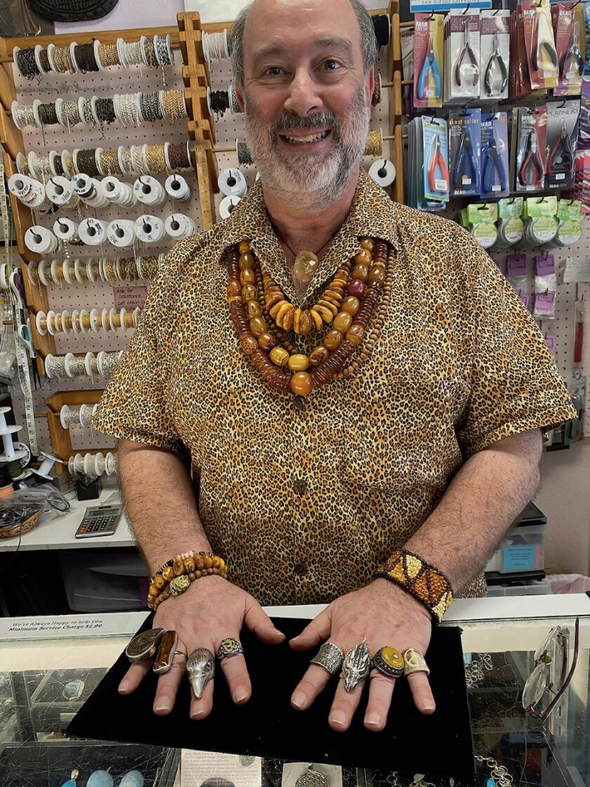 Phil Fischman, behind the counter at Beads, Crystals and More, wearing some of his favorite pieces.