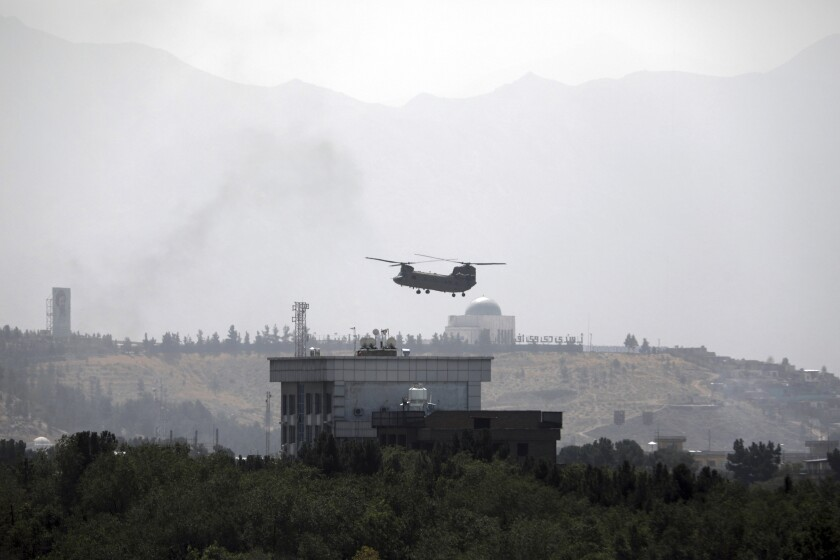 A U.S. helicopter flies over the U.S. Embassy in Kabul, Afghanistan, Sunday, Aug. 15, 2021.