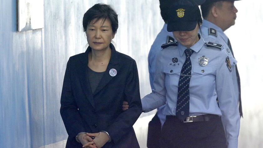Former South Korean President Park Geun-hye, left, arrives to attend a hearing on the extension of her detention at the Seoul Central District Court on Oct. 10, 2017.