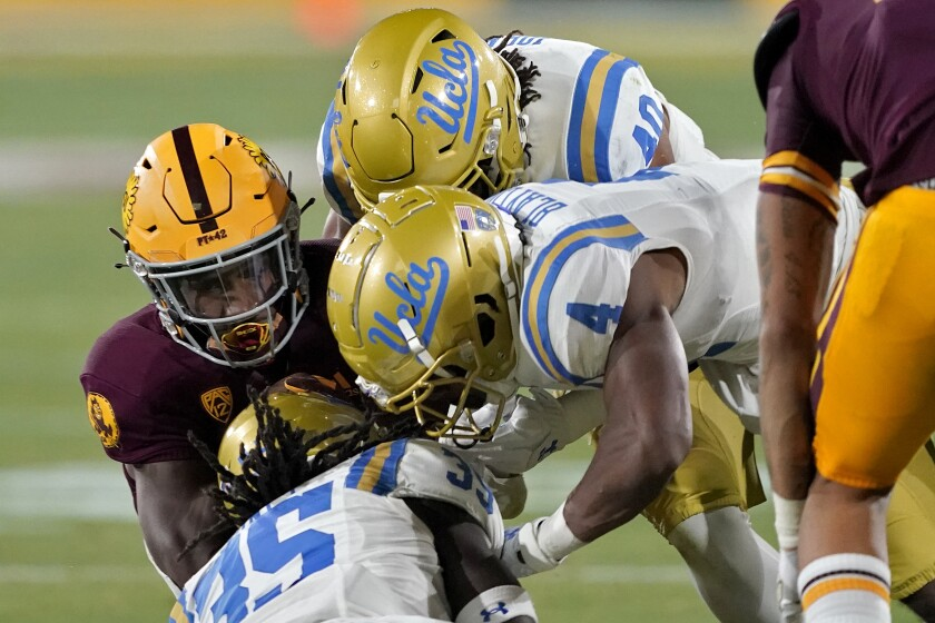 Arizona State running back Rachaad White, left, is hit by UCLA linebacker Carl Jones (35), defensive back Stephan Blaylock (4) and linebacker Caleb Johnson (40) during the first half of an NCAA college football game Saturday, Dec. 5, 2020, in Tempe, Ariz. (AP Photo/Matt York)