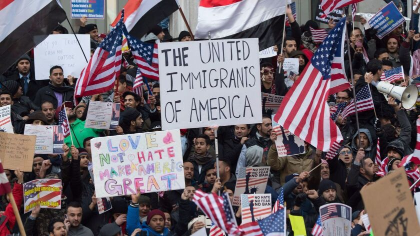Demonstrators at Brooklyn Borough Hall in New York rally to denounce President Trump's executive order limiting travel from seven countries.