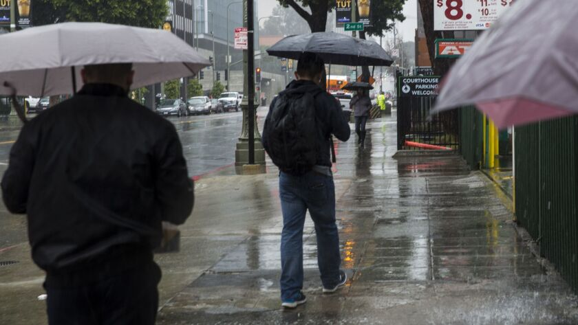 Pedestrians walk quickly in the rain in early March in downtown Los Angeles. Additional storms are expected into next week.