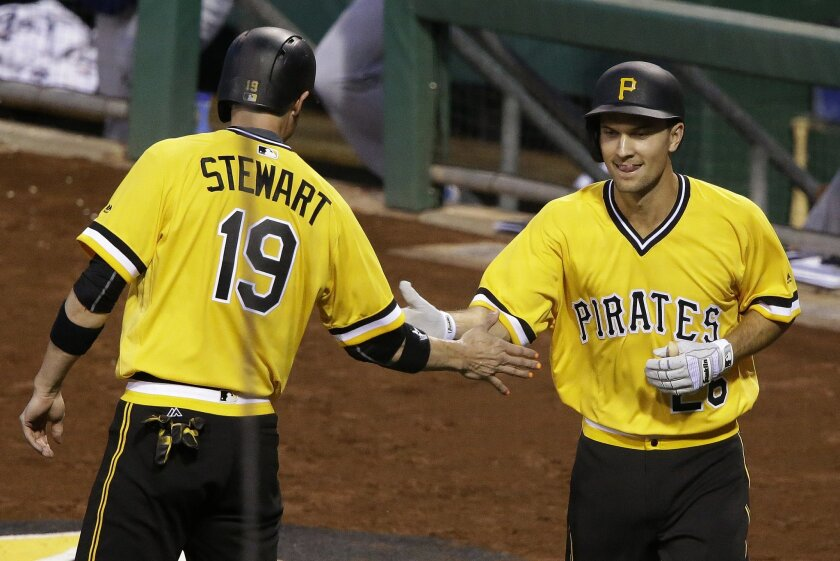 Pittsburgh Pirates' Adam Frazier, right, celebrates with teammate Chris Stewart (19) after both scored on a three-run double by Pirates' David Freese off Los Angeles Dodgers starting pitcher Clayton Kershaw in the second inning of a baseball game in Pittsburgh, Sunday, June 26, 2016. (AP Photo/Gene