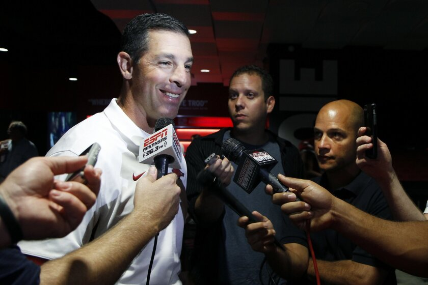 In this Aug. 9, 2015, photo, Arkansas offensive coordinator Dan Enos speaks to members of the media during an NCAA college football media day event in Fayetteville, Ark. Enos left his job as head coach at Central Michigan after last season to take over as the offensive coordinator for the No. 18 Razorbacks, who open their season against Texas-El Paso on Sept. 5. (AP Photo/Samantha Baker)