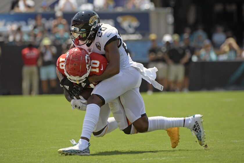 Chiefs wide receiver Tyreek Hill is stopped by Jaguars cornerback Jalen Ramsey after a reception during Sunday's game.