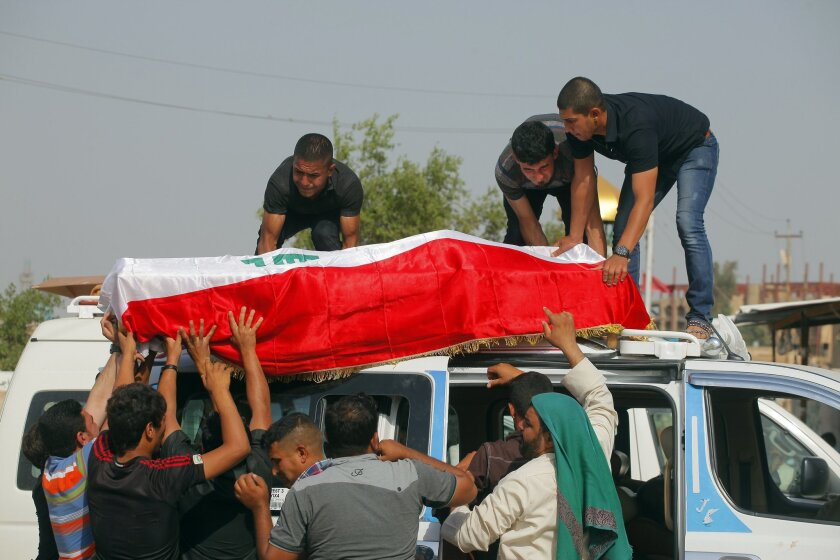 Family members of Ali Jamal, 23, who was killed in a bomb attack, load his flag-draped coffin onto a vehicle before burial in the Shiite holy city of Najaf, 100 miles (160 kilometers) south of Baghdad, Iraq, Monday, May 12, 2014. Bombings and shootings killed several people in areas south of the Ir