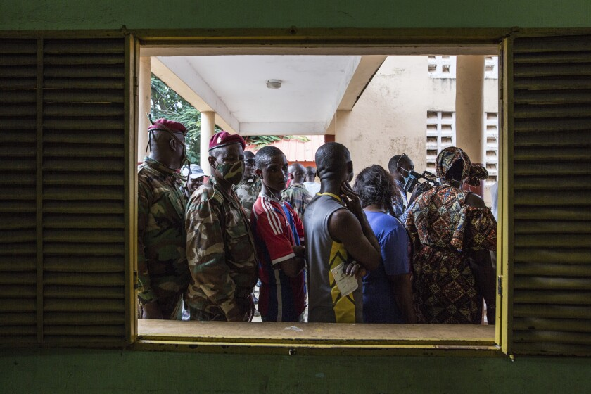 Civilians and soldiers line up to vote at a school in Conakry, Guinea, Sunday Oct. 18, 2020. Guineans head to the polls to elect their president, choosing between incumbent Alpha Conde who is seeking a third term and historical opponent Cellou Dalein Diallo. (AP Photo/Sadak Souici)