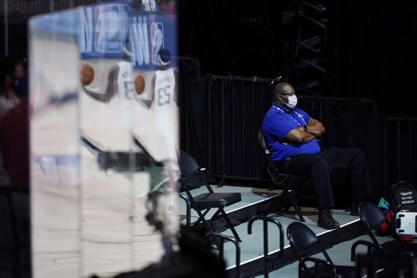 A man wearing a mask watches during halftime of an NBA basketball game between the Utah Jazz and the Oklahoma City Thunder, Saturday, Aug. 1, 2020, in Lake Buena Vista, Fla. (AP Photo/Ashley Landis, Pool)