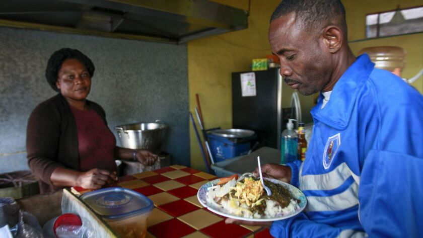 TIJUANA, November 28, 2018 | Kesmer Mollisoint, who is from Haiti, takes a plate of Haitian food co